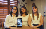 CORRECTS LOCATION - Dennysse Vadell sits between her daughters Veronica, right, and Cristina holding a digital photograph of father and husband Tomeu who is currently jailed in Venezuela, in Katy, Texas, Friday, Feb. 15, 2019. Tomeu Vadell is one of six executives from Houston-based Citgo who has spent 15 months jailed in Venezuela on what their families say are trumped-up corruption charges. (AP Photo/John L Mone)