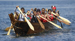 A tribal family pulls for shore during a stop on the annual tribal canoe journey through the Salish Sea Thursday, July 18, 2019, in Seattle. About 20 canoes from Northwest Native coastal tribes landed Thursday at Alki Beach on one of several legs of the canoe journey that gathers other canoe families from host tribes as they travel to a final landing, this year near Bellingham, Wash., at the Lummi Nation. (AP Photo/Elaine Thompson)
