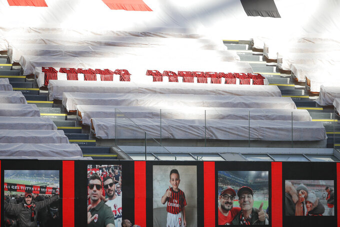 """Jerseys to honor the victims of COVID-19 are placed in the stands during the Serie A soccer match between AC Milan and Roma, at the San Siro Stadium in Milan, Sunday, June 28, 2020. It was Milan's first home match since the lockdown and the team put up a huge banner along one side of the empty San Siro stadium that read """"Together Forever,"""" dedicated to coronavirus victims. The Lombardy region of which Milan is the capital was the hardest hit area in Italy with more than 16,000 deaths. (AP Photo/Luca Bruno)"""