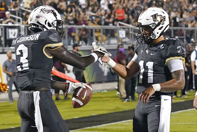 Central Florida wide receiver Brandon Johnson (3) celebrates his touchdown reception with quarterback Dillon Gabriel (11) during the first half of an NCAA college football game against Bethune-Cookman, Saturday, Sept. 11, 2021, in Orlando, Fla. (AP Photo/John Raoux)