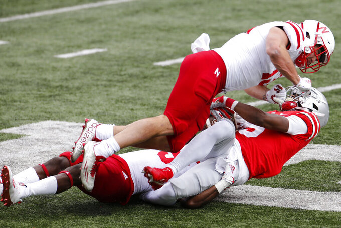 Nebraska linebacker JoJo Domann, top, and defensive back Marquel Dismuke, left, tackle Ohio State receiver Garrett Wilson during the first half of an NCAA college football game Saturday, Oct. 24, 2020, in Columbus, Ohio. (AP Photo/Jay LaPrete)