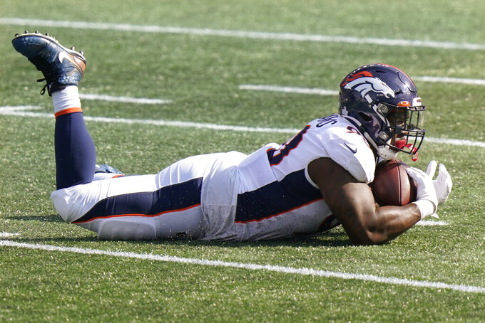 Denver Broncos defensive tackle DeShawn Williams cradles the ball after making an interception against the New England Patriots in the first half of an NFL football game, Sunday, Oct. 18, 2020, in Foxborough, Mass. (AP Photo/Steven Senne)