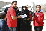 This photo released Tuesday March 13, 2018 by the Syrian Red Crescent, shows members of the Syrian Red Crescent help a woman who fled with her family from the fighting between Syrian government forces and rebels, in eastern Ghouta, a suburb of Damascus, Syria. Russian news agencies said at least 100 civilians have been evacuated from eastern Ghouta including 20 women and children. The Syrian government and the Russian military have set up a corridor outside eastern Ghouta to arrange the evacuation from the area which is home to some 400,000 people. (Syrian Red Crescent via AP)