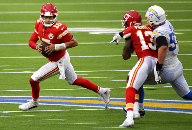 Quarterback Patrick Mahomes, left, of the Kansas City Chiefs scrambles against the Los Angeles Chargers in the second half of an NFL football game at SoFi Stadium in Inglewood, Calif., on Sunday, Sept. 20, 2020. Kansas City Chiefs won 23-20 in overtime. (Keith Birmingham/The Orange County Register via AP)