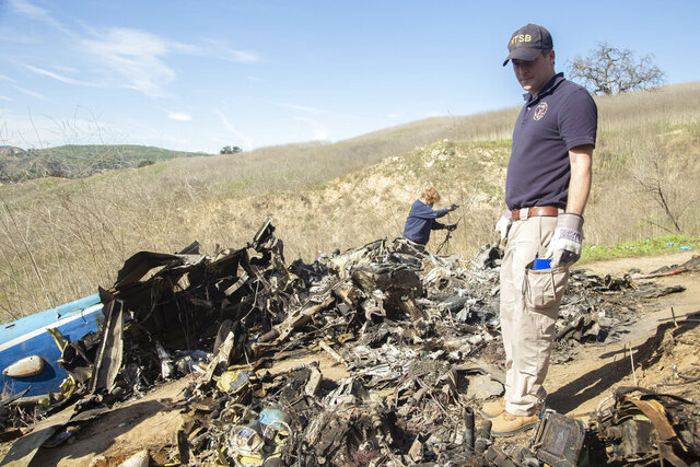 In this image taken Monday, Jan. 27, 2020, and provided by the National Transportation Safety Board, NTSB investigators Adam Huray, right, and Carol Hogan examine wreckage as part of the NTSB's investigation of a helicopter crash near Calabasas, Calif. The Sunday, Jan. 26 crash killed former NBA basketball player Kobe Bryant, his 13-year-old daughter, Gianna, and seven others (James Anderson/National Transportation Safety Board via AP)