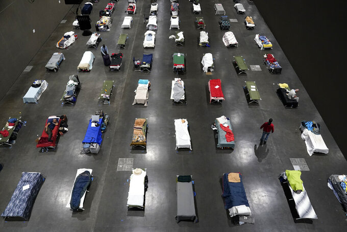 """FILE - In this Aug. 11, 2020, file photo, beds fill a homeless shelter inside the San Diego Convention Center in San Diego. A coalition in California is proposing legislation to boost taxes on wealthy multi-national corporations to raise more than $2 billion a year to end homelessness. Supporters say Assembly Bill 71, if approved, would """"reinvent"""" the state's approach to solving homelessness. (AP Photo/Gregory Bull, File)"""