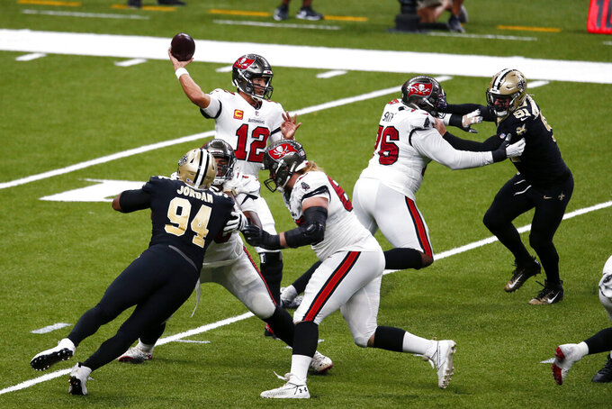 Tampa Bay Buccaneers quarterback Tom Brady (12) passes under pressure form New Orleans Saints defensive end Cameron Jordan (94) and defensive end Trey Hendrickson (91) in the second half of an NFL football game in New Orleans, Sunday, Sept. 13, 2020. (AP Photo/Butch Dill)