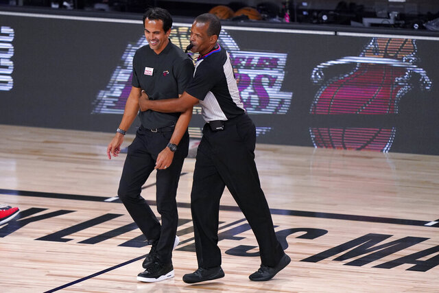 FILE - In this Oct. 2, 2020, file photo, Miami Heat coach Erik Spoelstra smiles as referee Eric Lewis (42) wraps his arms around Spoelstra during the second half of Game 2 of the basketball team's NBA Finals against the Los Angeles Lakers in Lake Buena Vista, Fla. NBA referees this season will have to adhere to new health and safety protocols, just like teams will in response to the coronavirus pandemic. (AP Photo/Mark J. Terrill, File)