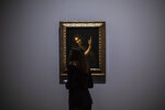 A journalist studies Saint Jean Baptiste artwork by Leonardo da Vinci during a visit at the Louvre museum Sunday, Oct. 20, 2019 in Paris. A unique group of artworks is displayed at the Louvre museum in addition to its collection of paintings and drawings by the Italian master. The exhibition opens to the public on Oct. 24, 2019. (AP Photo/Rafael Yaghobzadeh)