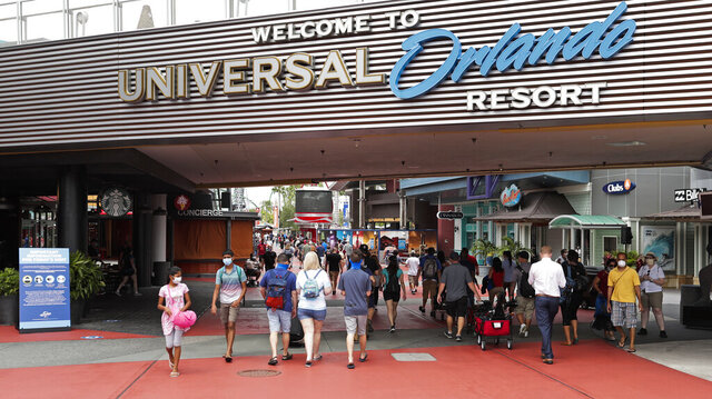In this Wednesday, June 3, 2020 photo, visitors arrive at Universal Studios Wednesday, June 3, 2020, in Orlando, Fla. The Universal Studios theme park has reopened for season pass holders and will open to the general public on Friday, June 5. (AP Photo/John Raoux)