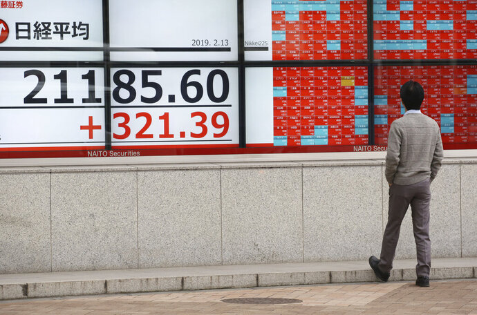 A man looks at an electronic stock board showing Nikkei Stock index, at a securities firm in Tokyo, Wednesday, Feb. 13, 2019.  Asian shares were mostly higher Wednesday, cheered by prospects for a resolution to the costly trade dispute between the U.S. and China, which had also sent Wall Street indexes higher. (AP Photo/Koji Sasahara)