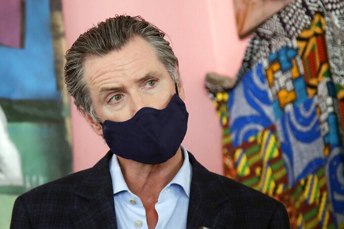 FILE - In this June 9, 2020, file photo, California Gov. Gavin Newsom wears a protective mask on his face while speaking to reporters at Miss Ollie's restaurant during the coronavirus outbreak in Oakland, Calif. Newsom has had a summer of muddled messaging and bad news in the coronavirus fight, a trend crystallized by the governor's delayed response to a data error that caused a backlog of nearly 300,000 virus test results. (AP Photo/Jeff Chiu, Pool, File)