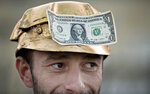 FILE - In this Saturday, Sept. 21, 2013 file photo, a man wears a dollar bill on a miner's helmet painted in the color of gold during a protest in Bucharest, Romania. Rosia Montana, the site of ancient Roman mining galleries in a mountainous western Romanian region and home to Europe's largest gold deposits, an estimated 314 tonnes, which was set to be exploited over a 16-year period by Gabriel Resources, a Canadian mining company that gained concession rights to the area in 1999, was added to UNESCO's World Heritage list Tuesday, July 27, 2021. (AP Photo/Vadim Ghirda, File)