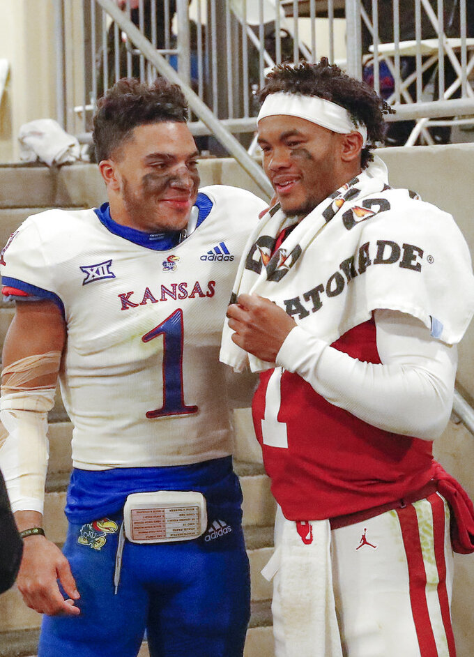Kansas safety Bryce Torneden, left, and Oklahoma quarterback Kyler Murray, right, meet outside the Kansas locker room following an NCAA college football game in Norman, Okla., Saturday, Nov. 17, 2018. Oklahoma won 55-40. (AP Photo/Alonzo Adams)
