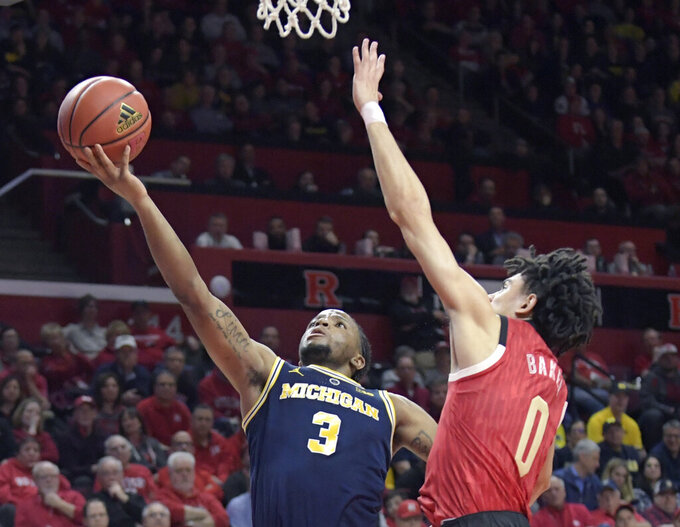 Michigan guard Zavier Simpson (3) shoots as Rutgers guard Geo Baker (0) defends during the first half of an NCAA college basketball game Tuesday, Feb. 5, 2019, in Piscataway, N.J. (AP Photo/Bill Kostroun)