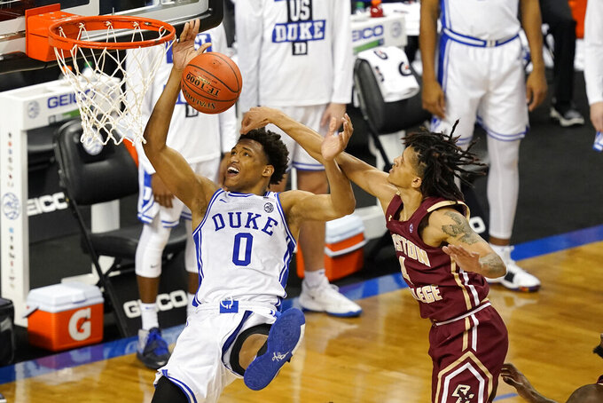 Duke forward Wendell Moore Jr. (0) looses the handle as he drives to the basket as Boston guard Makai Ashton-Langford (4) fouls during the second half of an NCAA college basketball game in the first round of the Atlantic Coast Conference tournament in Greensboro, N.C., Tuesday, March 9, 2021. (AP Photo/Gerry Broome)