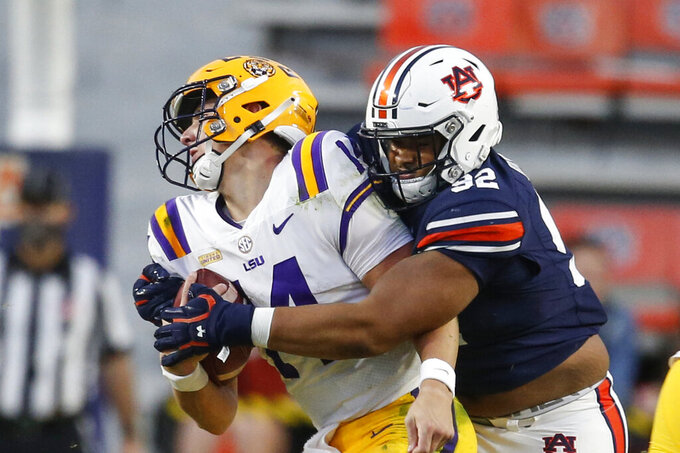 LSU quarterback Max Johnson (14) is sacked by Auburn defensive tackle Marquis Burks (92) during the second half of an NCAA college football game on Saturday, Oct. 31, 2020, in Auburn, Ala. (AP Photo/Butch Dill)