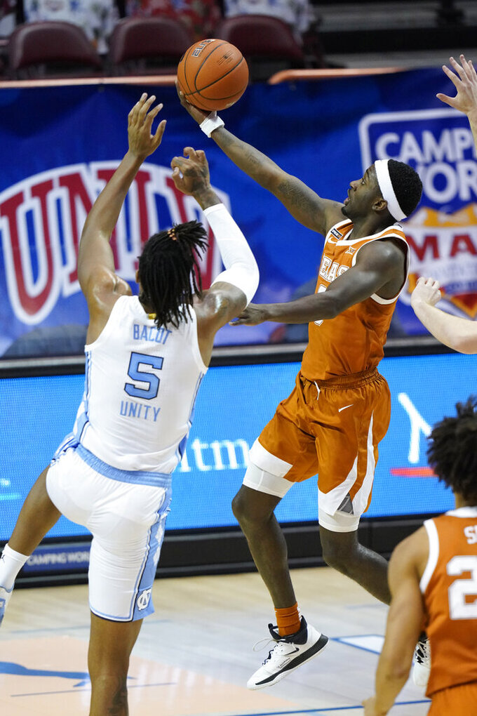 Texas guard Courtney Ramey (3) goes up for a basket against North Carolina forward Armando Bacot (5) in the second half of an NCAA college basketball game for the championship of the Maui Invitational, Wednesday, Dec. 2, 2020, in Asheville, N.C. Texas won 69-67. (AP Photo/Kathy Kmonicek)
