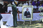 A soldier stands next to a portrait of former Zimbabwean President Robert Mugabe during mass at his rural home in Zvimba, about 100 kilometers north west of the capital Harare, Saturday. Sept, 28, 2019. According to a family spokesperson Mugabe is expected to be buried at the residence after weeks of drama mystery and contention over his burial place. (AP Photo/Tsvangirayi Mukwazhi)