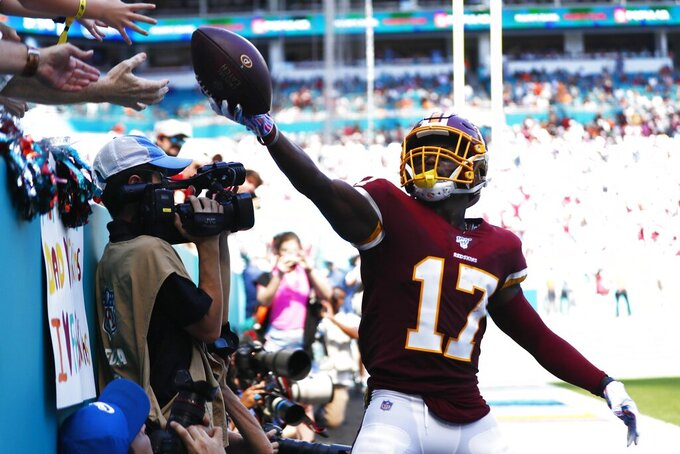 Washington Redskins wide receiver Terry McLaurin (17) gives away the football after scoring a touchdown, during the first half at an NFL football game against the Miami Dolphins, Sunday, Oct. 13, 2019, in Miami Gardens, Fla. (AP Photo/Brynn Anderson)