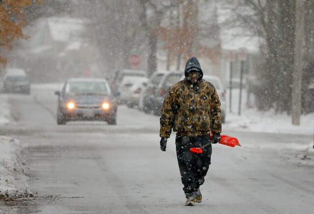 Bill Parham walks down an icy street in Maplewood, Mo., looking to clear snow off people's driveways and sidewalks on Monday, Dec. 16, 2019. The wintry weather was part of a storm system that hit parts of the Midwest and was expected to extend into the Northeast through Tuesday, the National Weather Service said. (David Carson/St. Louis Post-Dispatch via AP)