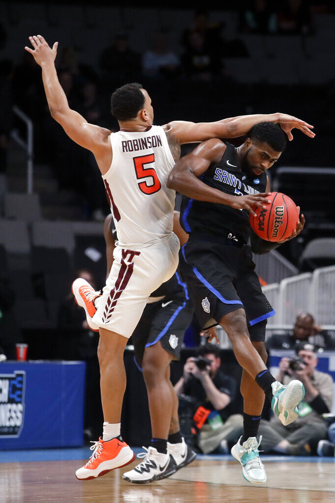 Saint Louis guard Tramaine Isabell Jr., right, catches a pass next to Virginia Tech guard Justin Robinson during the second half of a first-round game in the NCAA men's college basketball tournament Friday, March 22, 2019, in San Jose, Calif. (AP Photo/Jeff Chiu)
