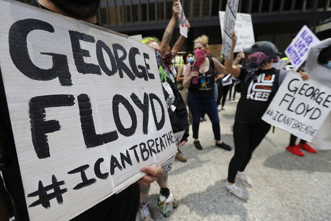 Protesters hold signs before they march during a protest over the death of George Floyd in Chicago, Saturday, May 30, 2020. Floyd died after being taken into custody and restrained by Minneapolis police on Memorial Day in Minnesota. (AP Photo/Nam Y. Huh)
