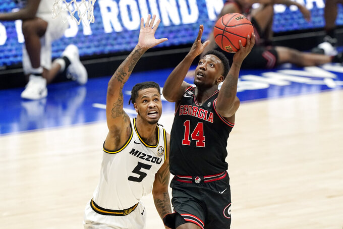 Georgia's Tye Fagan (14) drives against Missouri's Mitchell Smith (5) in the first half of an NCAA college basketball game in the Southeastern Conference Tournament Thursday, March 11, 2021, in Nashville, Tenn. (AP Photo/Mark Humphrey)
