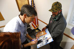 Former Texas congressman Beto O'Rourke autographs a photo after speaking at the International Brotherhood of Electrical Workers Local 13 hall, Thursday, March 14, 2019, in Burlington, Iowa. O'Rourke announced Thursday that he'll seek the 2020 Democratic presidential nomination. (AP Photo/Charlie Neibergall)