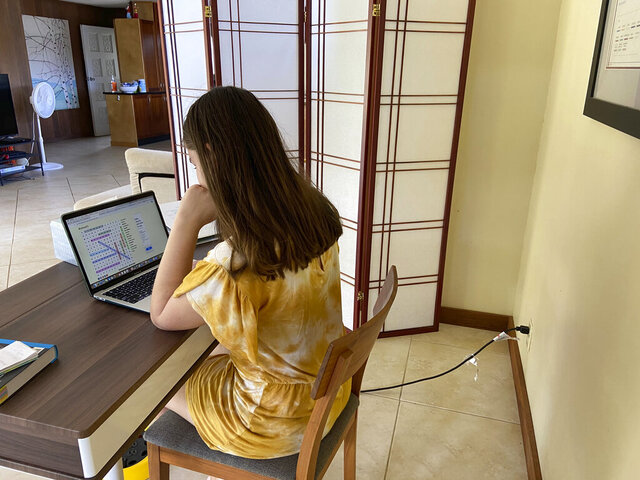 FILE - This file photo provided by Adrienne Robillard shows her daughter, name withheld by parent, doing school work at a computer at home in Kailua, Hawaii, Friday, Sept. 18, 2020. Hawaii's Department of Education is recommending that the state's public schools stop using a distance learning program that parents said had contained racist and sexist content. Schools across the nation have been using Acellus for distance learning and some have dropped the program after parent complaints. (Adrienne Robillard via AP, File)