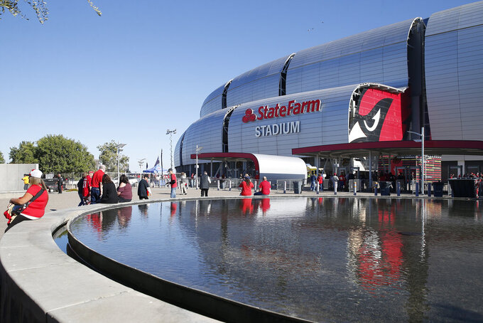 FILE - In this Thursday, Oct. 31, 2019, file photo, fans arrive prior to an NFL football game at State Farm Stadium in Glendale, Ariz. Governor Doug Ducey and the Arizona Department of Health Services announced Friday, Jan. 8, 2021, that Arizona will open a 24/7 vaccination site Monday, Jan. 11, 2021 at State Farm Stadium to dramatically expand the availability of COVID-19 vaccine doses in the Phoenix metropolitan area. (AP Photo/Rick Scuteri, File)