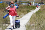 Jody Curran wears a protective mask due to the COVID-19 virus outbreak as she walks on a one way pathway towards Good Harbor Beach in Gloucester, Mass., Friday, May 22, 2020. Beaches in Gloucester reopened with restrictions on Friday after being closed two months ago due to the pandemic. (AP Photo/Charles Krupa)