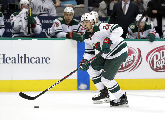 FILE - In this Saturday, March 31, 2018 file photo, Minnesota Wild's Matt Dumba handles the puck during an NHL hockey game in Dallas. Minnesota's Matt Dumba has won the King Clancy Memorial Trophy awarded for leading on and off the ice and making humanitarian contributions to his community. Dumba, who is Filipino-Canadian, in August became the first NHL player to kneel during the U.S. anthem (AP Photo/Tony Gutierrez, File)