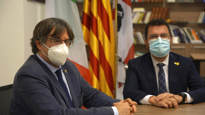 Catalan separatist leader Carles Puigdemont, left, meets with Catalonia's president Pere Aragones, in the Sardinian city of Alghero, Italy, Saturday, Sept. 25, 2021, a day after a judge freed him from jail pending a hearing on his extradition to Spain, where the political firebrand is wanted for sedition. (AP Photo/Andrea Rosa)