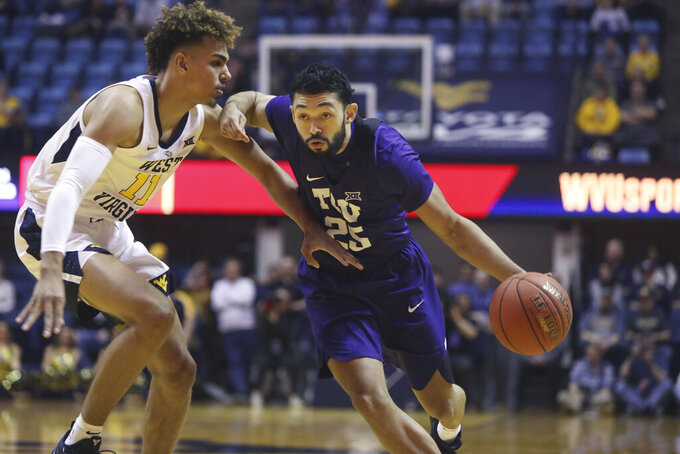 TCU guard Alex Robinson (25) drives while defended by West Virginia forward Emmitt Matthews Jr. (11) during the first half of an NCAA college basketball game Tuesday, Feb. 26, 2019, in Morgantown, W.Va. (AP Photo/Raymond Thompson)