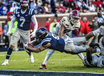 Mississippi running back Jerrion Ealy (9) dives over New Mexico State defensive back Austin Shaw (13) to score in the second quarter of an NCAA college football game in Oxford, Miss., Saturday, Nov. 9, 2019. (Jackson Newman/The Oxford Eagle via AP)