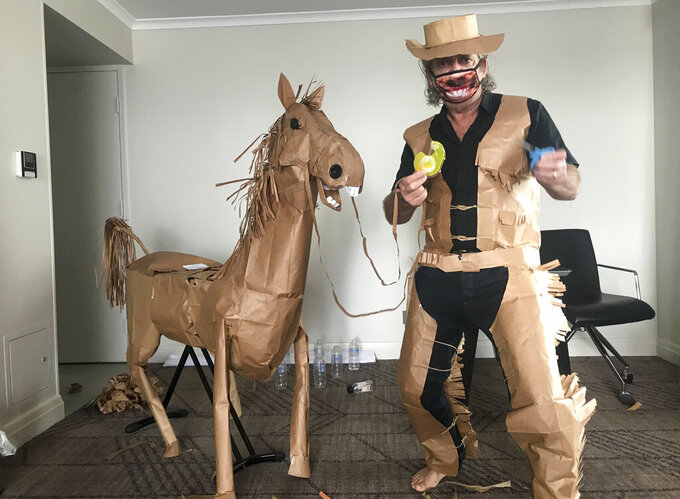 "CORRECTS NAME - David Marriott poses with his paper horse ""Russell"" in his hotel room in Brisbane, Australia, April 1, 2021. While in quarantine inside his Brisbane hotel room, the art director was bored and started making a cowboy outfit from the paper bags his meals were being delivered in. His project expanded to include a horse and a clingfilm villain that he has daily adventures with, in images that have gained a huge online following. (David Marriott via AP)"