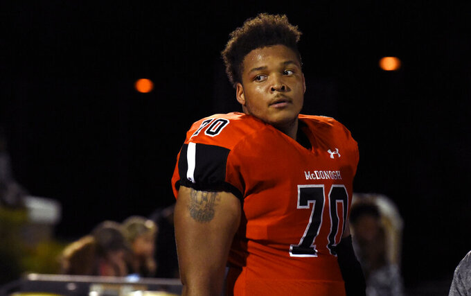 FILE - In this Sept. 16, 2016, file photo, McDonogh high school football lineman Jordan McNair watches from the sideline during a game in McDonogh, Md. University of Maryland President Wallace Loh will remain at the state's flagship university through June 2020, after he initially announced plans to retire at the end of this school year in the aftermath of the death of football player Jordan McNair. Board of Regents Chair Linda Gooden announced Wednesday, Jan. 30, 2019 that Loh is leading several initiatives critical to the university's future.  (Barbara Haddock Taylor/The Baltimore Sun via AP, File)