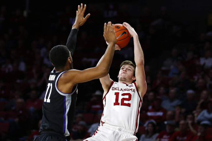 Oklahoma guard Austin Reaves (12) shoots as Kansas State forward Antonio Gordon (11) defends in the second half of an NCAA college basketball game in Norman, Okla., Saturday, Jan. 4, 2020. (AP Photo/Sue Ogrocki)