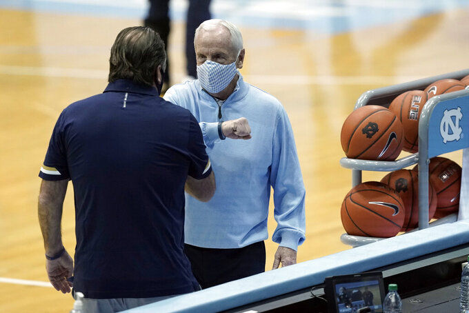 North Carolina head coach Roy Williams, right, and Notre Dame head coach Mike Brey speak prior to an NCAA college basketball game in Chapel Hill, N.C., Saturday, Jan. 2, 2021. (AP Photo/Gerry Broome)