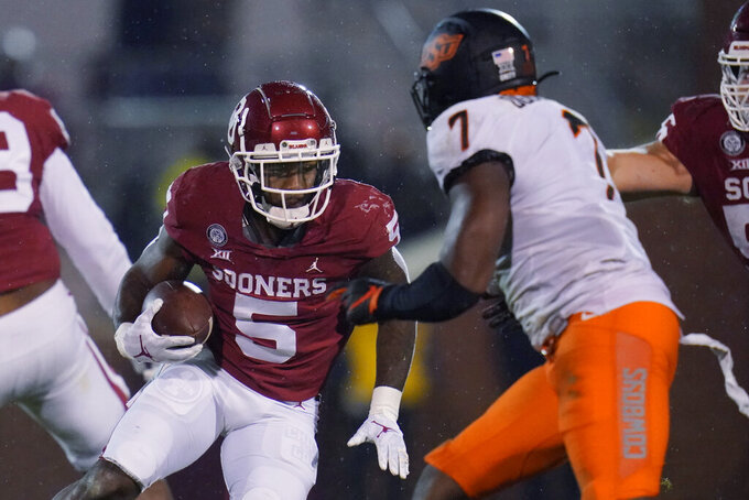 Oklahoma running back T.J. Pledger (5) carries as Oklahoma State linebacker Amen Ogbongbemiga (7) defends during the second half of an NCAA college football game in Norman, Okla., Saturday, Nov. 21, 2020. (AP Photo/Sue Ogrocki)