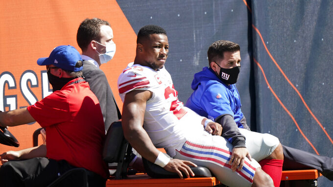 FILE - New York Giants running back Saquon Barkley (26) is carted to the locker room after being injured during the first half of an NFL football game against the Chicago Bears in Chicago, in this Sunday, Sept. 20, 2020, file photo. Coming off an ACL injury that cost him most of last season, Saquon Barkley either doesn't know or isn't saying how much he will be able to do when the New York Giants report to training camp next week. Speaking during a break at a youth football camp Monday, July 19, 2021, Barkley said he is continuing to rehabilitate his right knee and he is taking things day by day. (AP Photo/Nam Y. Huh, File)