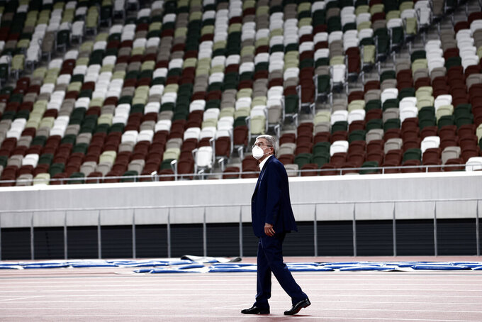 "IOC President Thomas Bach visits the National Stadium, the main venue for the 2020 Olympic and Paralympic Games postponed until July 2021 due to the coronavirus pandemic, in Tokyo Tuesday, Nov. 17, 2020. Bach said during this week's trip to Tokyo that he is ""encouraging"" all Olympic ""participants"" and fans to be vaccinated - if one becomes available - if they are going to attend next year's Tokyo Olympics. (Behrouz Mehri/Pool Photo via AP)"