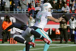 Miami Dolphins quarterback Ryan Fitzpatrick flips a pass as New England Patriots linebacker Jamie Collins, left, flies past in the first half of an NFL football game, Sunday, Dec. 29, 2019, in Foxborough, Mass. (AP Photo/Charles Krupa)