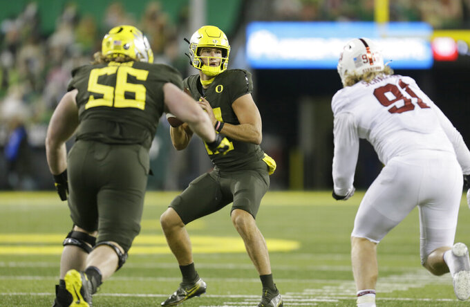 Oregon's Tyler Shough, center, drops back to pass under pressure during the fourth quarter of an NCAA college football game against Stanford, Saturday, Nov. 7, 2020, in Eugene, Ore. (AP Photo/Chris Pietsch)