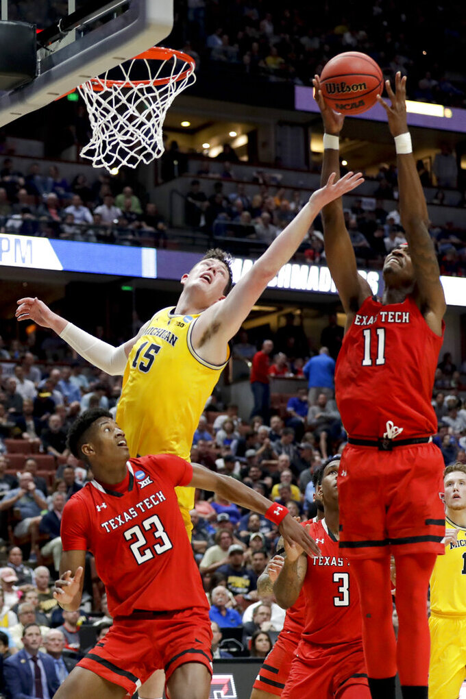Michigan center Jon Teske, left, vies for a rebound with Texas Tech forward Tariq Owens as Jarrett Culver watches during the first half an NCAA men's college basketball tournament West Region semifinal Thursday, March 28, 2019, in Anaheim, Calif. (AP Photo/Marcio Jose Sanchez)