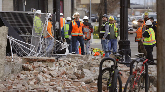 Construction workers looks at the rubble from a building after an earthquake Wednesday, March 18, 2020, in Salt Lake City.  A 5.7-magnitude earthquake has shaken the city and many of its suburbs. The quake sent panicked residents running to the streets, knocked out power to tens of thousands of homes and closed the city's airport and its light rail system.  (AP Photo/Rick Bowmer)