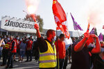 Bridgestone employees gather outside the tire factory of Bethune, northern France, Thursday, Sept.17, 2020. Workers protest over the Japan-based company's decision to close the plant and lay off all its nearly 900 workers. Bridgestone argues the factory is no longer competitive globally, but unions and French politicians accused the company of using the virus-driven economic crisis as a pretext for the closure and not investing in modernizing the plant instead. (AP Photo/Michel Spingler)