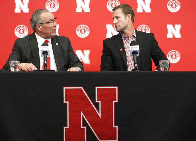 In this photo taken April 2, 2019, Nebraska athletic director Bill Moos, left, introduces Fred Hoiberg as Nebraska's new NCAA college basketball head coach at a news conference in Lincoln, Neb. Moos has pulled off two of the splashiest hires in college athletics in the 18 months since he arrived. He brought Scott Frost back to his alma mater after he coached Central Florida to an unbeaten season in 2017. This week he hired former Iowa State star player and coach Hoiberg. (AP Photo/Nati Harnik)