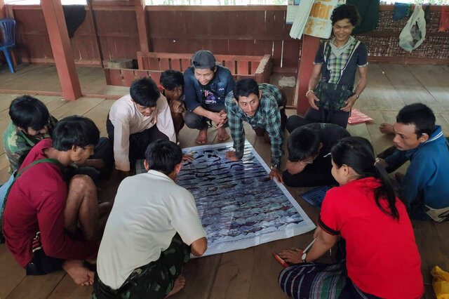 """In this March 2020 photo provided by the Southern Youth Development Organization, community members check information contained in a poster they produced which documents local fish, before publication, in the Lenya area of the Tanintharyi region in southern Myanmar. After learning about the UN's """"Ridge to Reef"""" conservation project, indigenous land rights activists spent nearly a year consulting with local communities to develop an alternative proposal for a landscape conserved by indigenous people, outlining techniques used for generations, including land and forest administration as well as traditional customs and practices that safeguard biodiversity. (Southern Youth Development Organization via AP)"""
